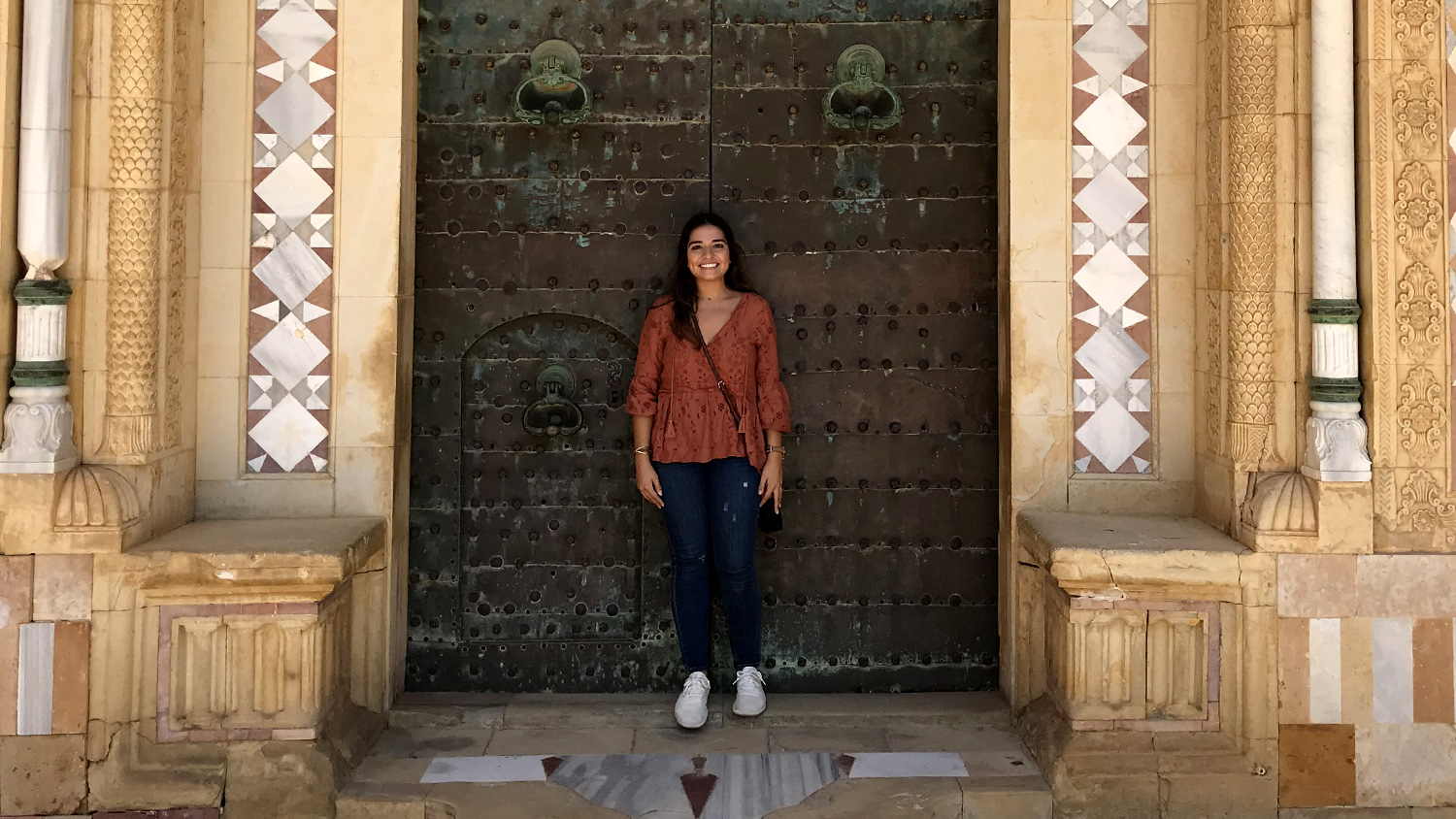 A student poses in front of a doorway during a study abroad trip