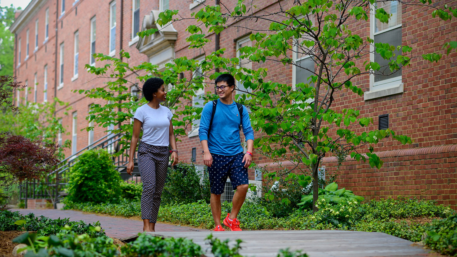 Undergraduate students gather by flowers near Tucker beach and in between residence halls on main campus