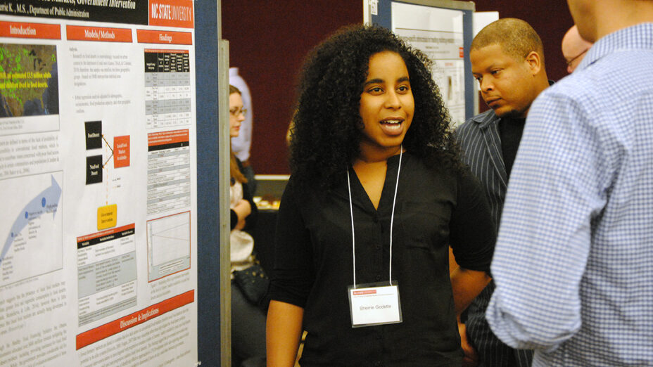 A student presents a research poster