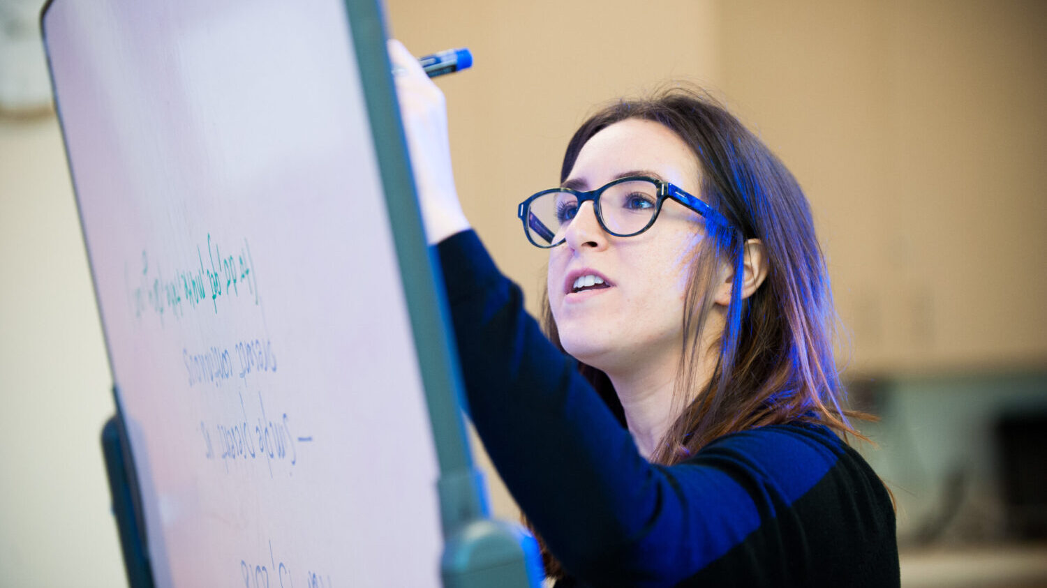 A student writes on a whiteboard