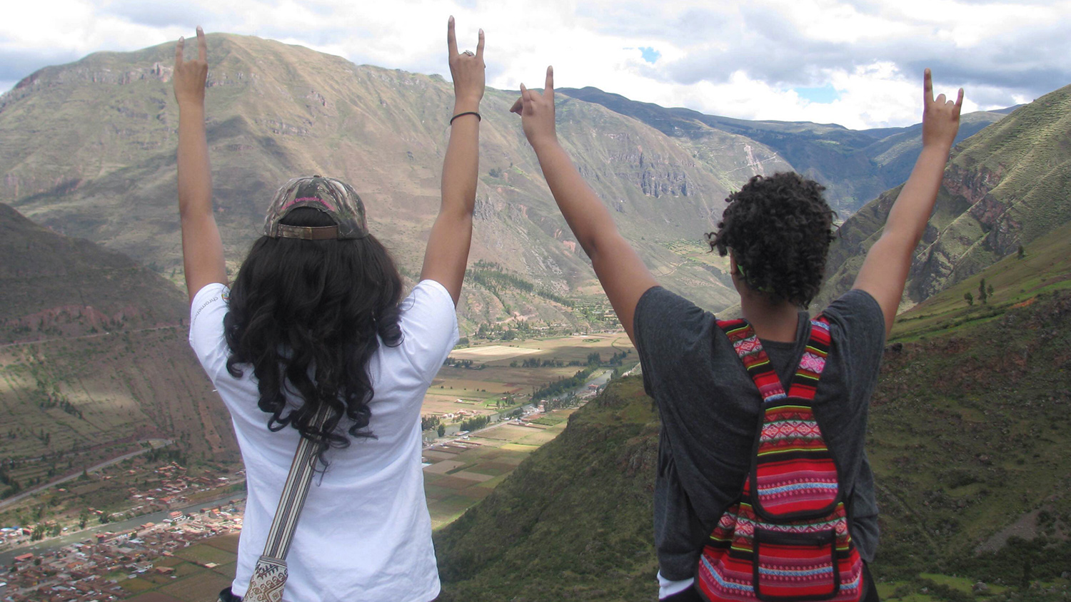 two students hold up wolfies on mountain top