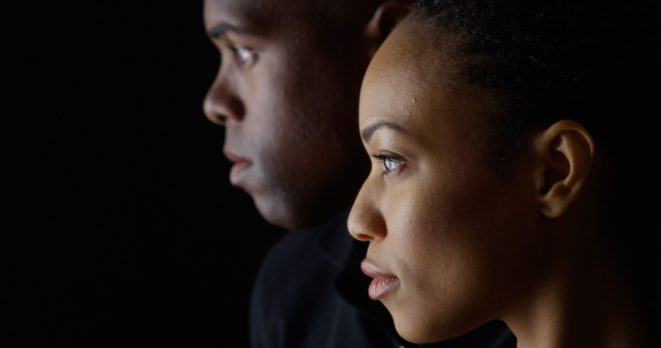 Dramatic profile rack focus of two young black people