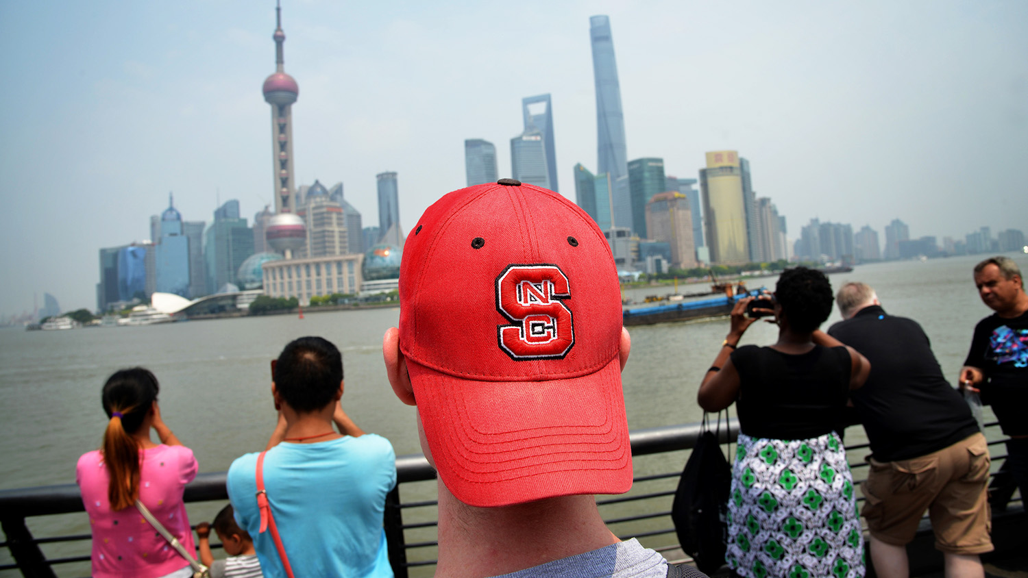 student with NCState hat looks at buildings in Shanghai