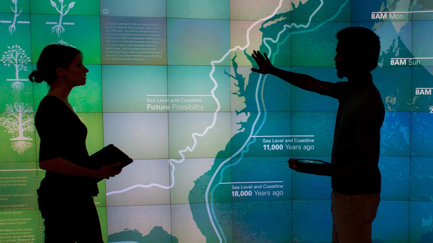 Two students work at a large visualization screen