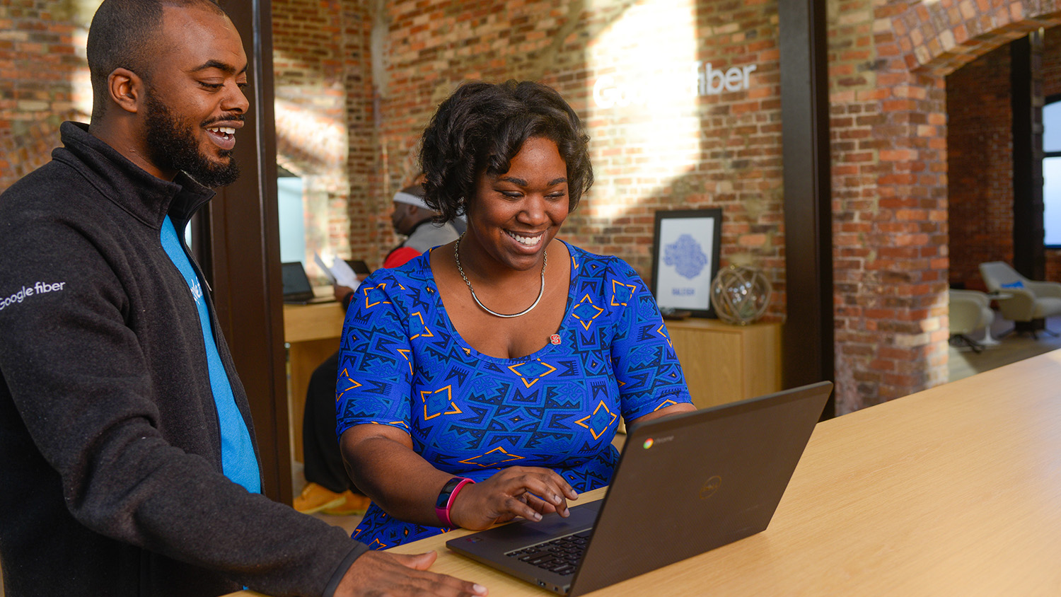 Two people smile while looking at a laptop