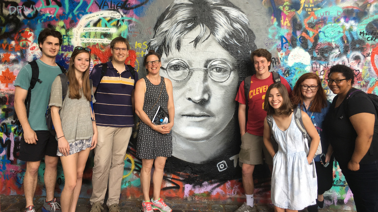 Group photo of NCState sudents gathered in front of a mural in Prague
