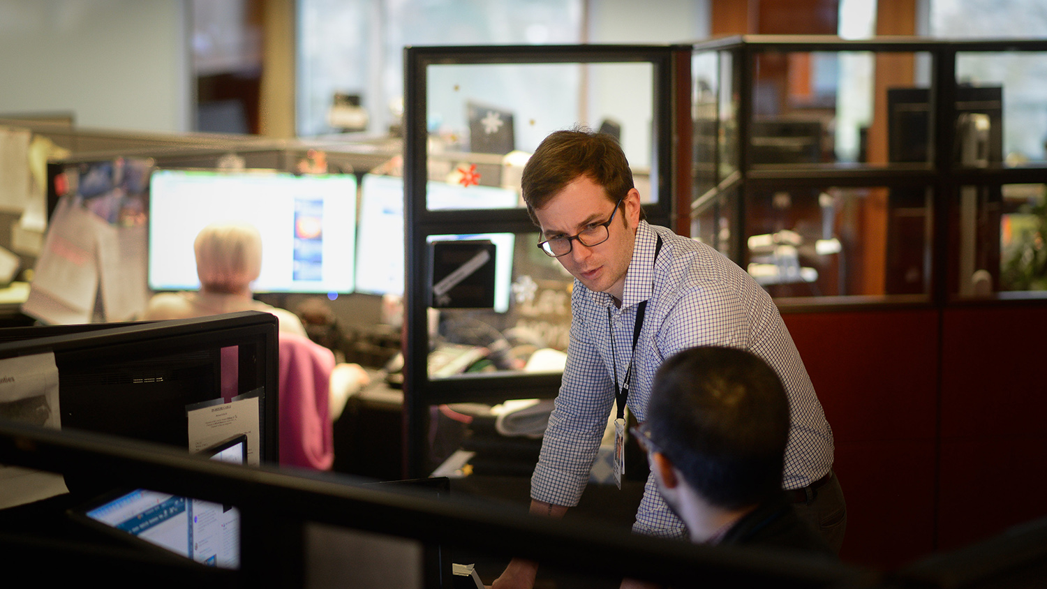 Tyler Dukes talks to a coworker in the newsroom