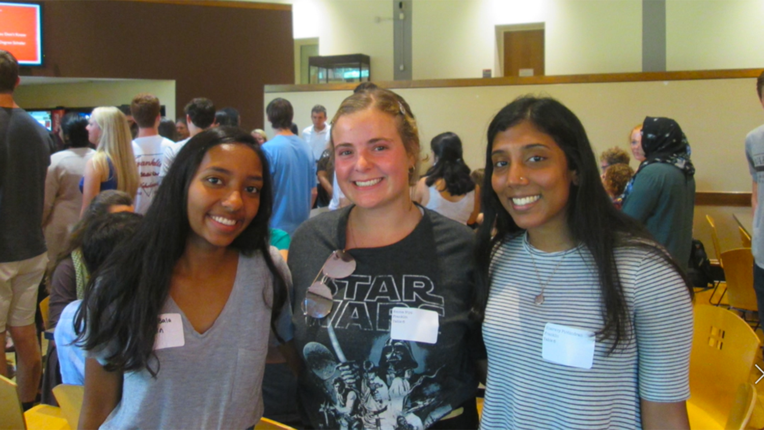 three students standing in Caldwell Lounge